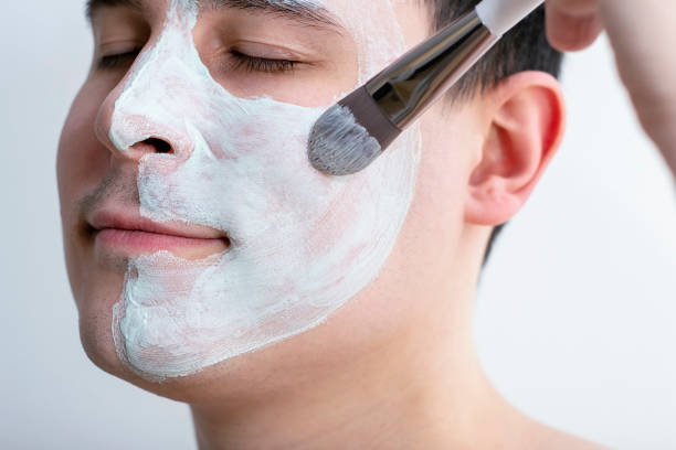 Man with a mask on his face. Applying the mask with a brush on the face. Cosmetics for men. Relaxation from cosmetic procedures. Cleaning the face mask. stock photo