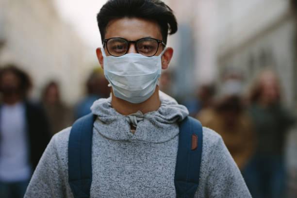 hombre con máscara participando en una protesta - civil rights fotografías e imágenes de stock