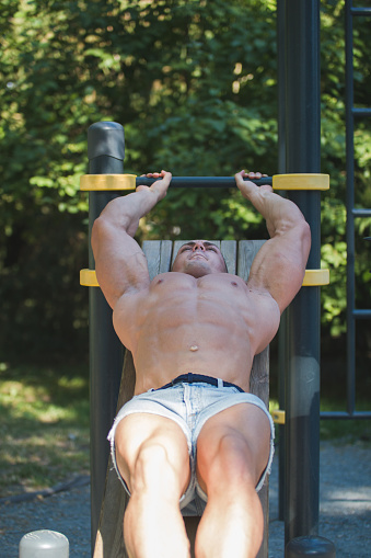 A Man With A Muscular Inflated Body Performs Exercises On