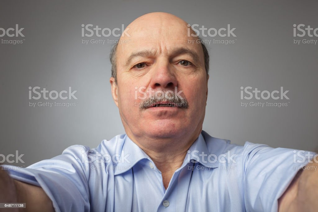 A man with a mustache, holding something in his hands gently, afraid to drop stock photo