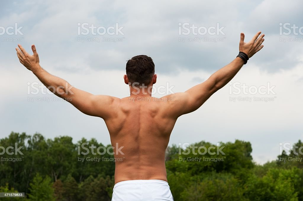 Man with a naked torso stands and his hands up stock photo