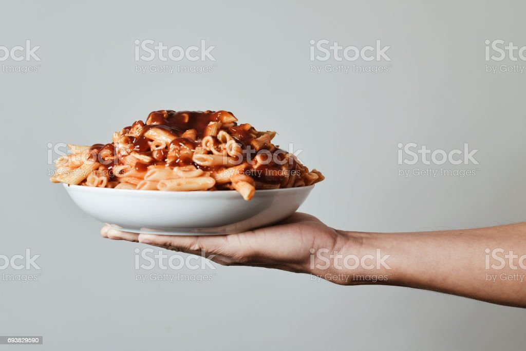 man with a plate of pasta with tomato sauce stock photo