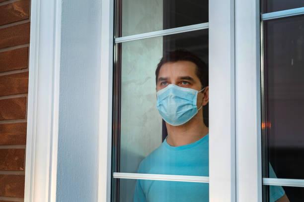 Mann mit medizinischer Schutzmaske am Fenster – Foto