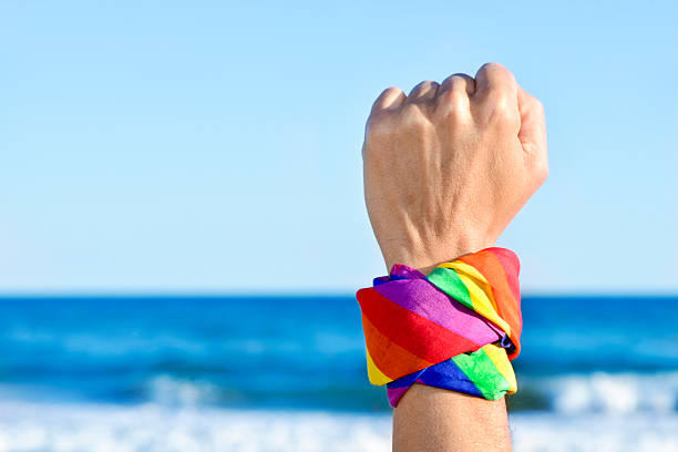 man with a rainbow-patterned kerchief in his wrist closeup of a young caucasian man with his fist raised to the sky and a kerchief patterned as the rainbow flag tied in it, with the ocean in the background gay pride parade stock pictures, royalty-free photos & images