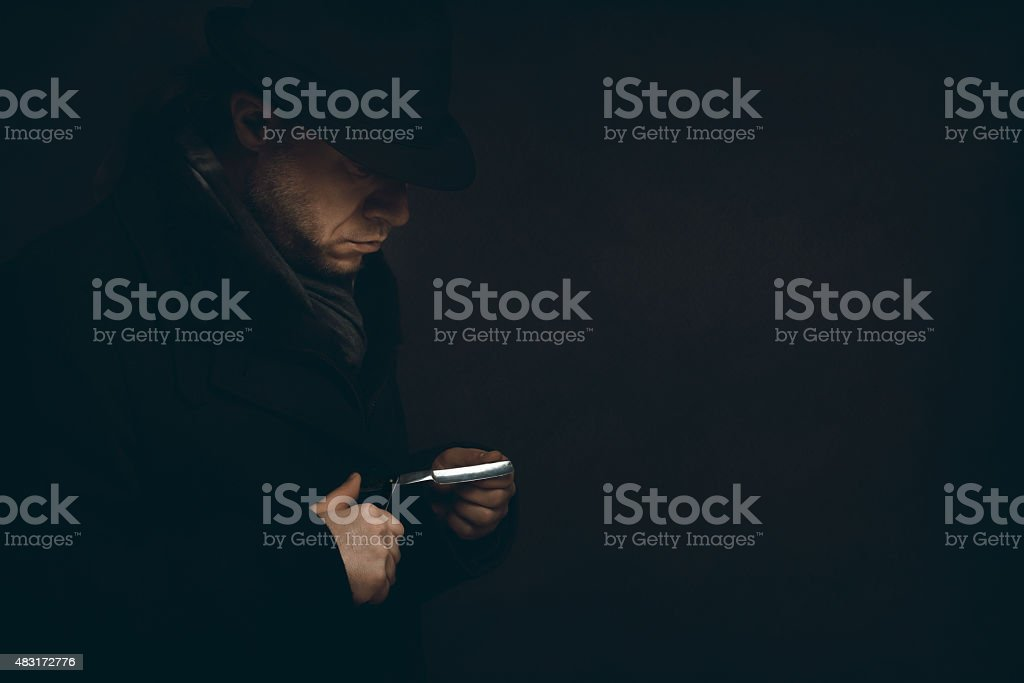 Man with a razor is waiting in the dark stock photo