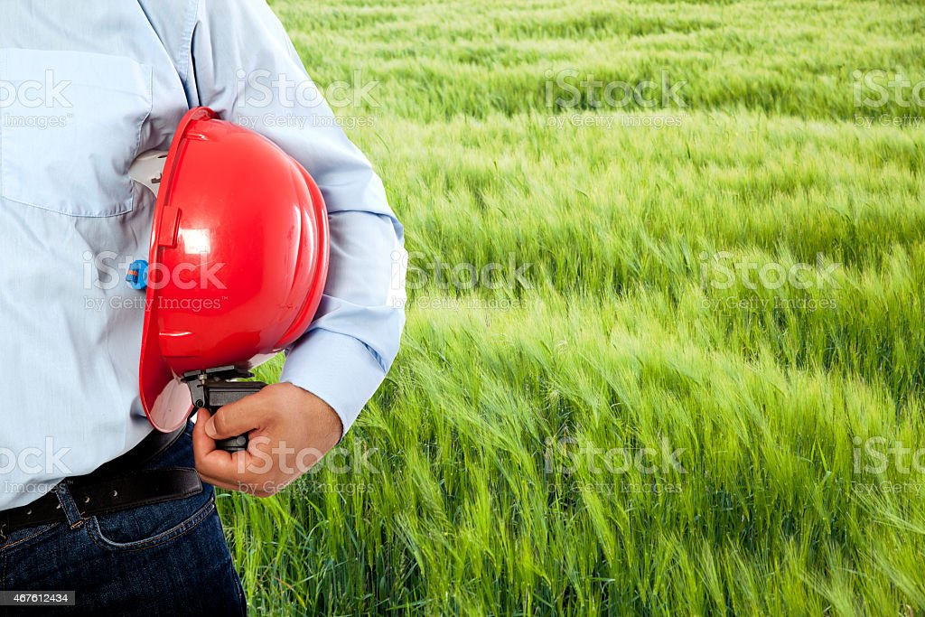 A man with a red hat under his arm In a field stock photo