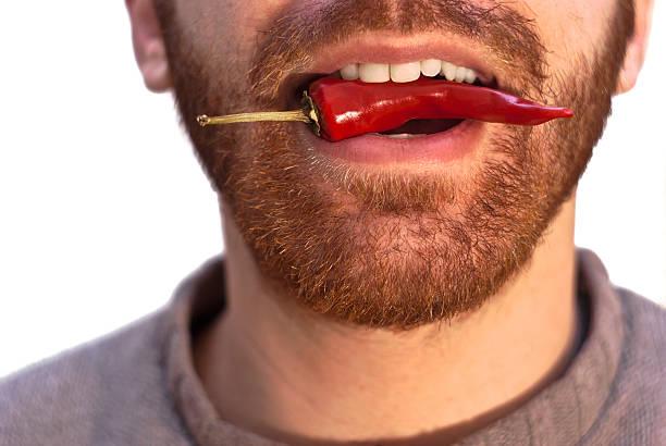 Uomo con un rosso caldo Peperoncino in sua bocca - foto stock