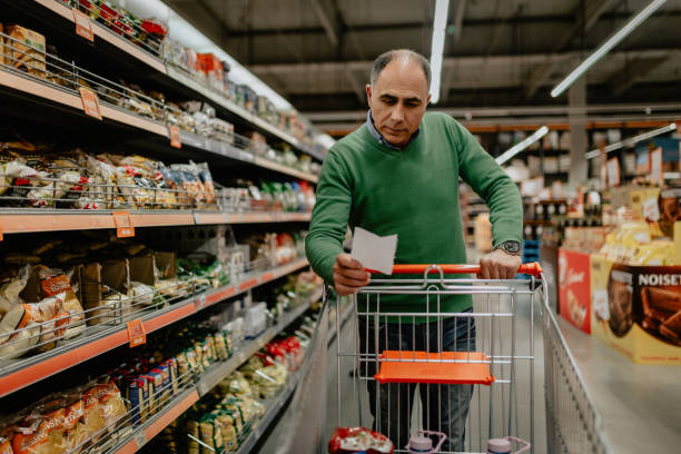 Man with a shopping list buying groceries in the supermarket stock photo