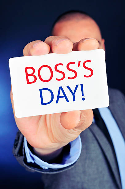 man with a signboard with the text boss day a young caucasian businessman shows a signboard with the text boss day written in it boss's day stock pictures, royalty-free photos & images