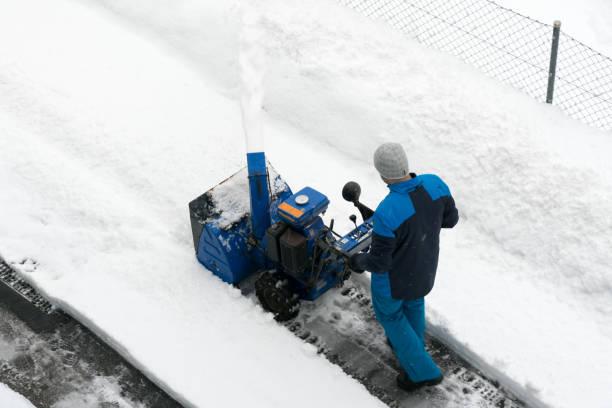 Mann mit einer Schneefräse löscht Schnee von einer Straße nach starkem Schneefall – Foto