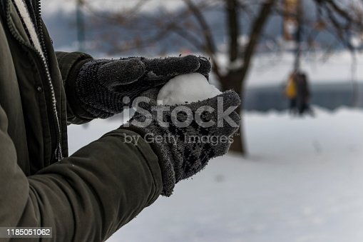 Close View of Male with Gloves in Warm Clothing Holding a Snowball in his Hands During a Winter Day in Park Covered with Snow