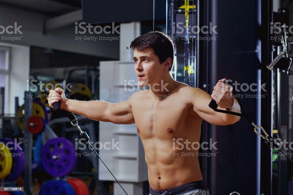Homem com uma figura de esportes fazendo exercício no simulador no ginásio - foto de acervo