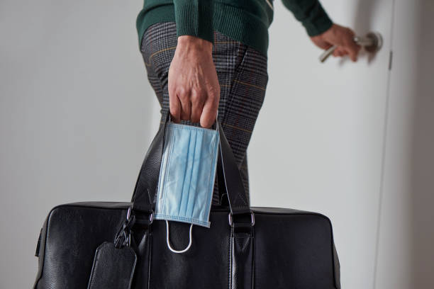 man with a suitcase and a surgical mask stock photo