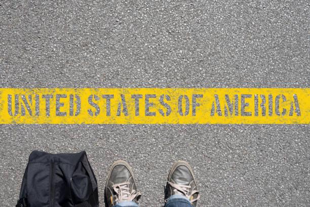 Ein Mann mit Koffer an der Grenze von Amerika Ein Mann mit Koffer an der Grenze von Amerika green card stock pictures, royalty-free photos & images