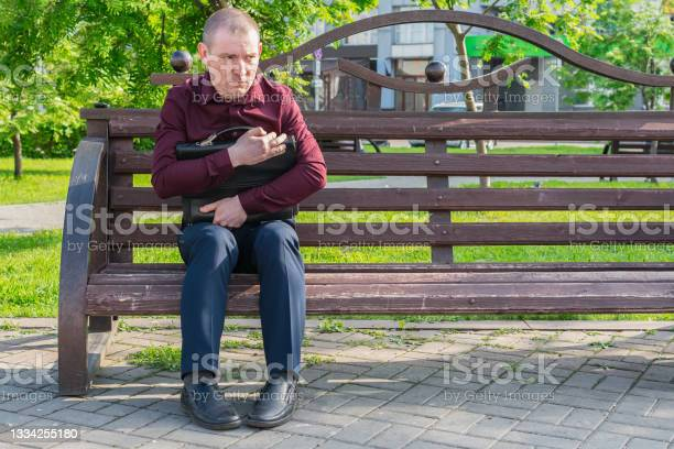 Photo of A man with a suitcase sits on a park bench