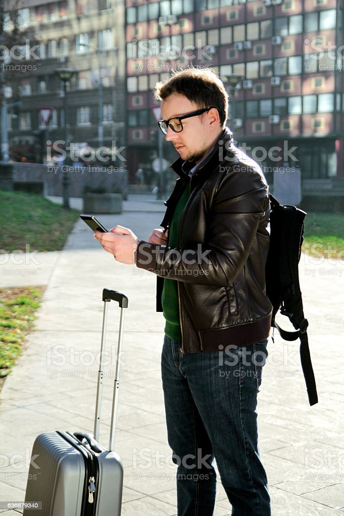 Man with a suitcase standing and using smartphones outdoor - foto de acervo