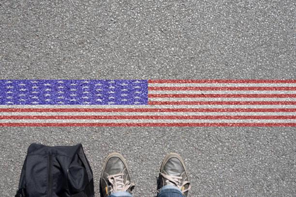 Ein Mann mit dem Koffer steht an der Grenze zu USA Ein Mann mit dem Koffer steht an der Grenze zu USA green card stock pictures, royalty-free photos & images
