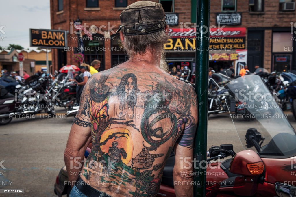 Man with a tattoed back looking at the bikes in the city of Sturgis, South Dakota, USA, during the annual Sturgis Motorcycle Rally stock photo