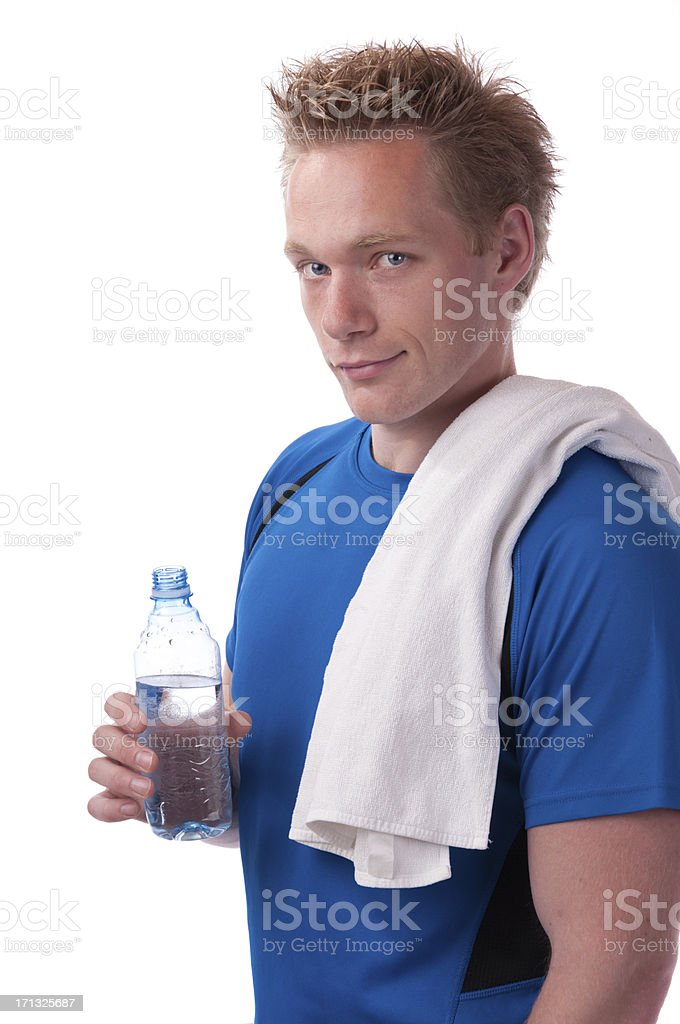 Man with a towel over his shoulder and holding a bottle of water while smirking at the camera. stock photo