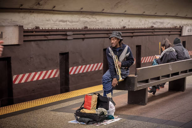 Man, with a trumpet taking a break in a subway Station stock photo