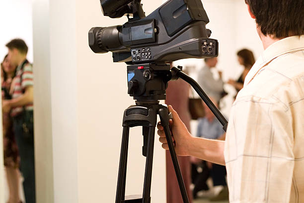 A man with a video camera set up at an event stock photo