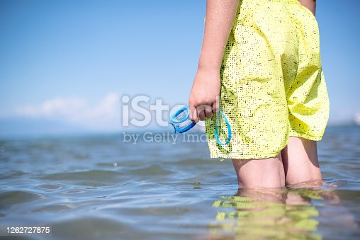 Man with a yellow swimwear is holding goggles in his hand and going into a sea