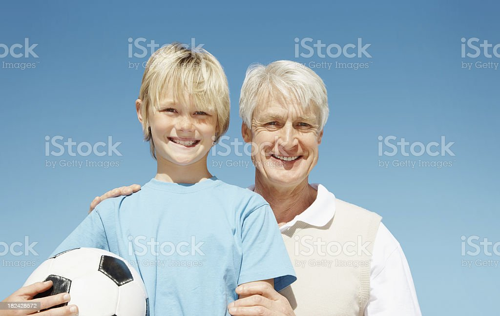 Man with a young boy holding football against blue sky royalty-free stock photo
