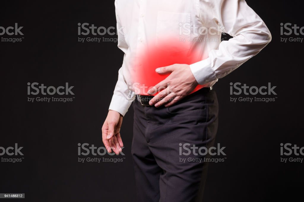 Man with abdominal pain, stomach ache on black background stock photo