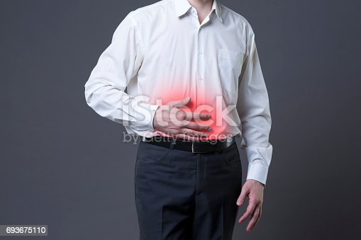 istock Man with abdominal pain, stomach ache on gray background 693675110