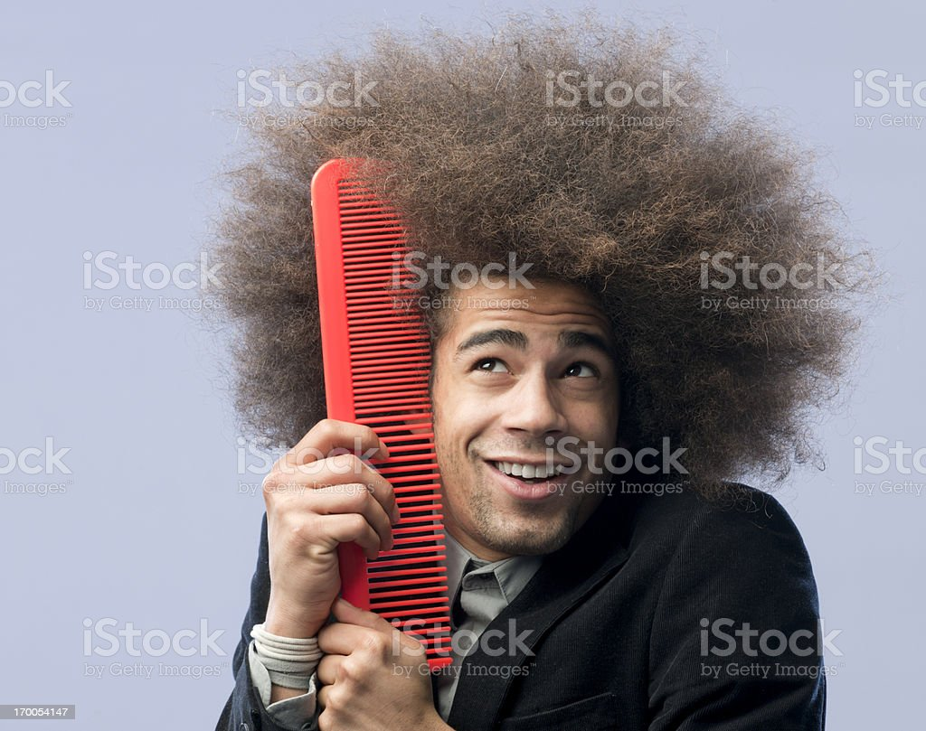 man with afro hair holding red comb to his face stock photo