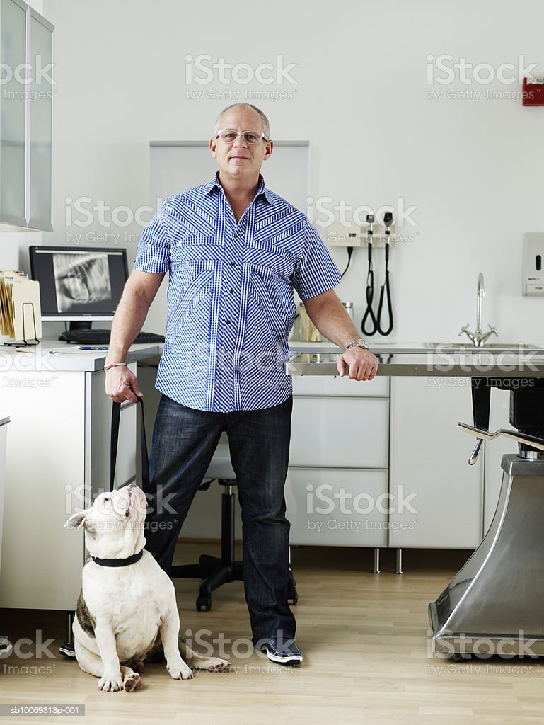 Man with American bulldog in veterinarian exam room 免版稅 stock photo