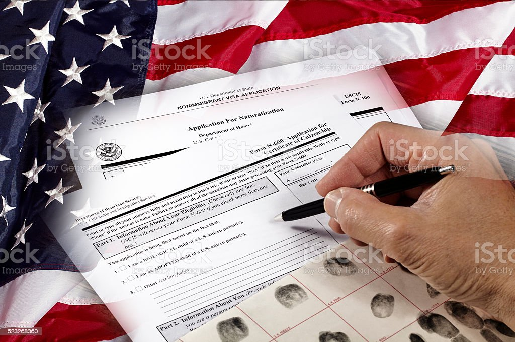 Man with American citizenship application on USA flag stock photo