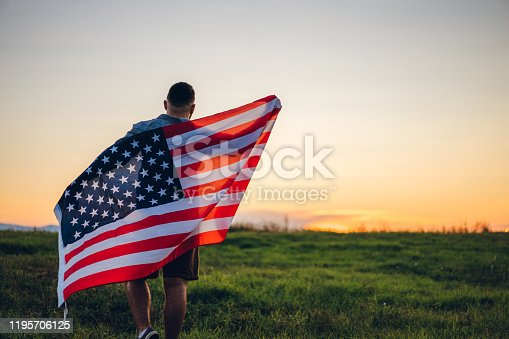Young Caucasian man with American flag on meadow at sunset.