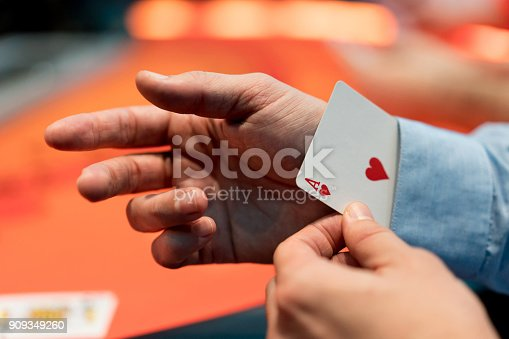 Close-up on a man with an ace under his sleeve while playing poker at the casino