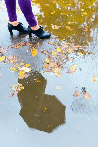 ein mann mit einem regenschirm spiegelt sich in einer pfütze. - damenschuhe k stock-fotos und bilder