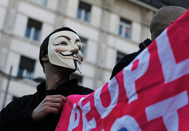 man with anonymous mask, holding banner - guy fawkes mask stock photos and pictures