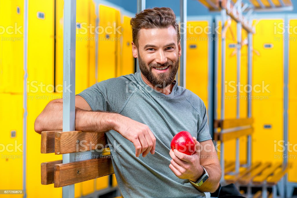 Man with apple in the gym stock photo
