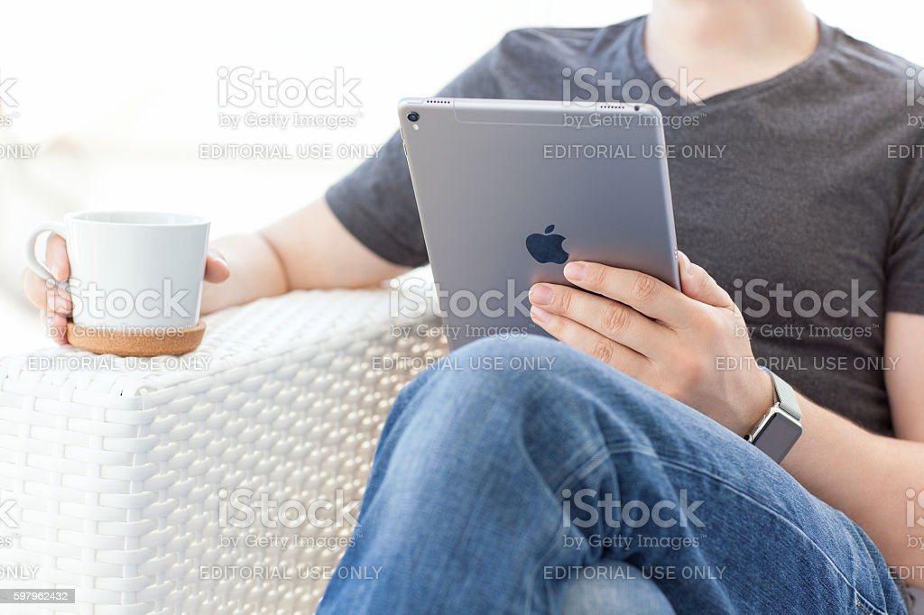 Man with Apple Watch holding in hand new iPad Pro stock photo