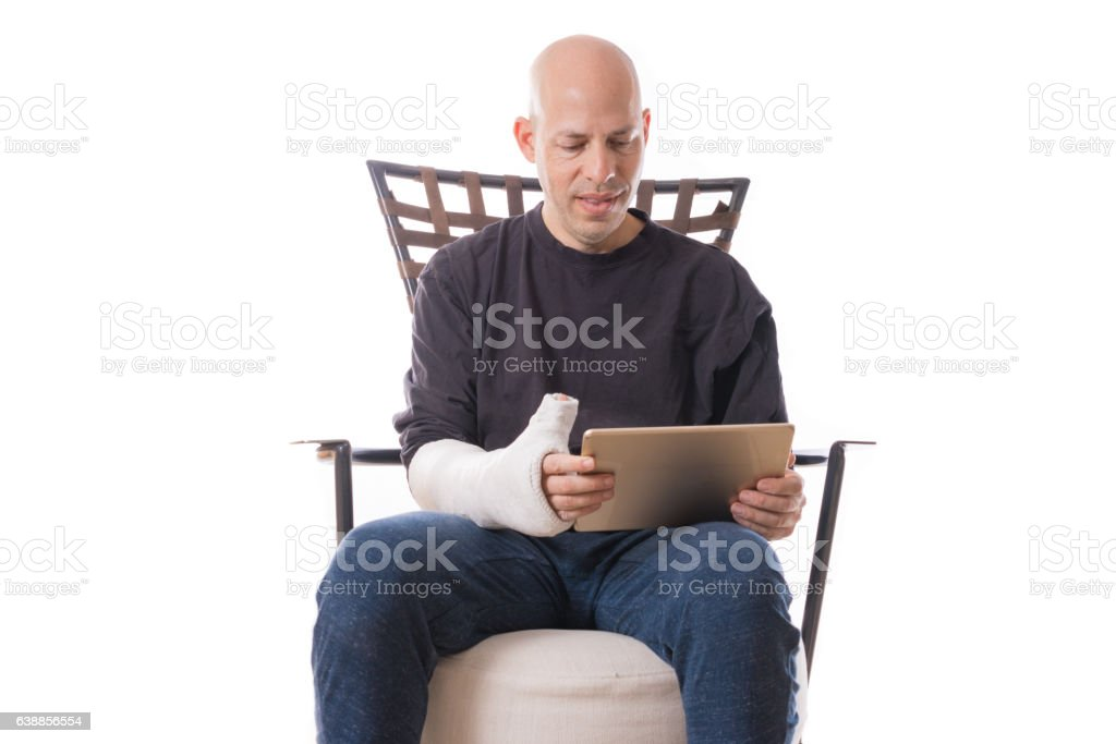 Man with arm cast using an accessible tablet stock photo