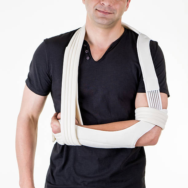man with arm supported in sling in white studio. - shoulder surgery stock photos and pictures