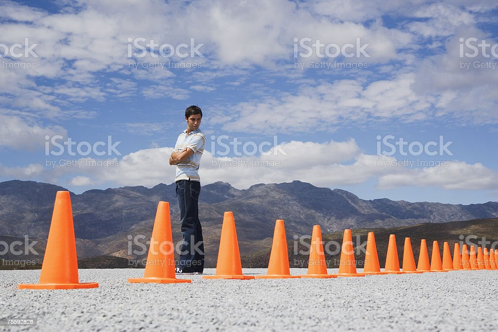 Man with arms crossed looking at traffic cones in line outdoors ground level view royalty-free stock photo