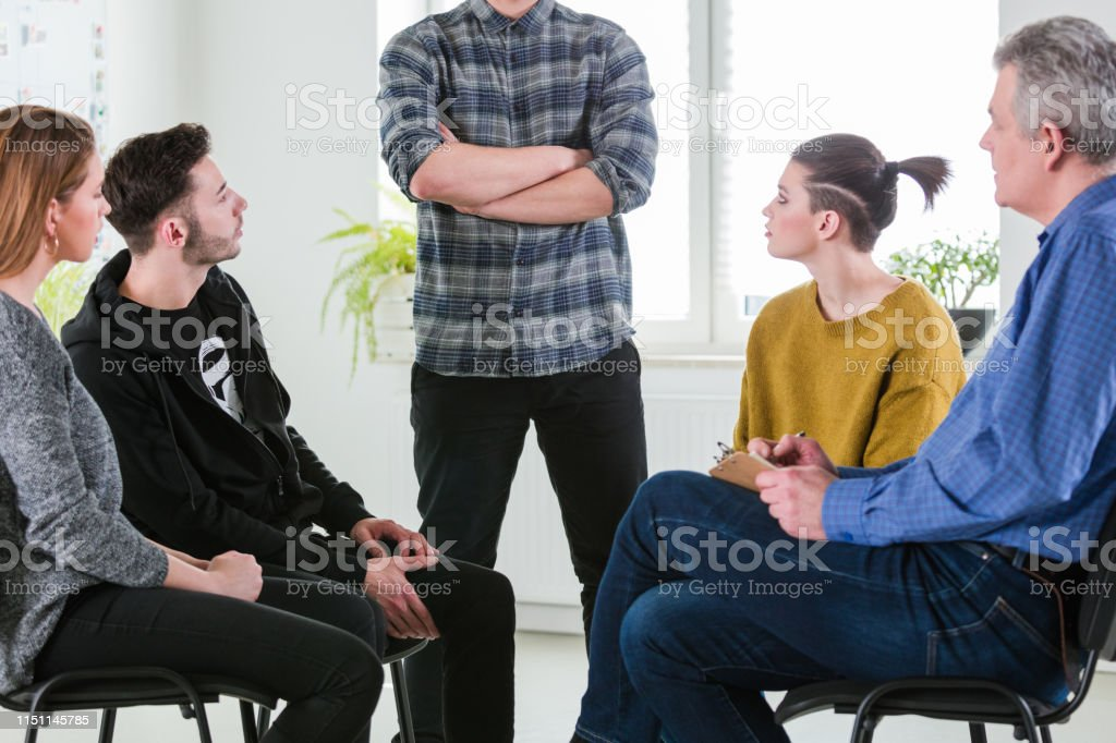 Man with arms crossed sharing problems in therapy Young man with arms crossed sharing problems in mental health session. University students and therapist are in lecture hall. They are wearing casuals. 18-19 Years Stock Photo