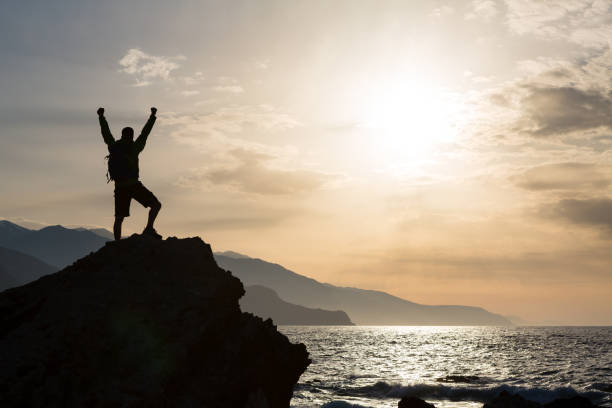 Man with arms outstretched celebrate mountains sunrise stock photo
