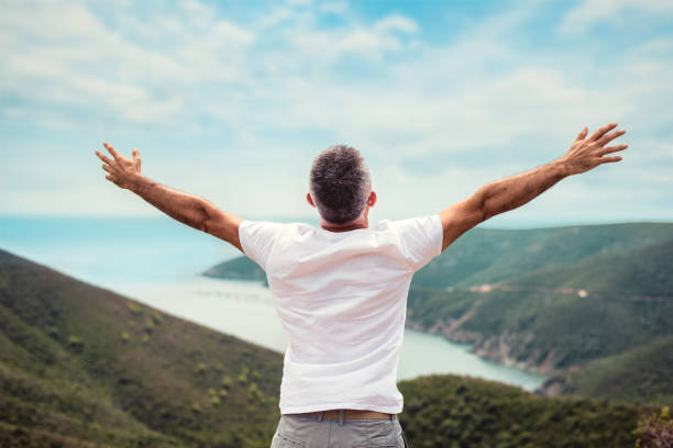 Man with arms outstretched on mountaintop Man with arms outstretched on mountaintop arms outstretched stock pictures, royalty-free photos & images