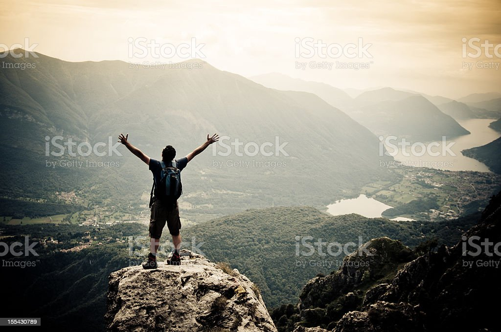 Man with arms outstretched on mountaintop stock photo