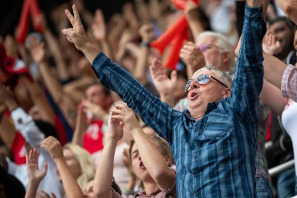 man with arms raised in a stadium crowd - adeptos imagens e fotografias de stock