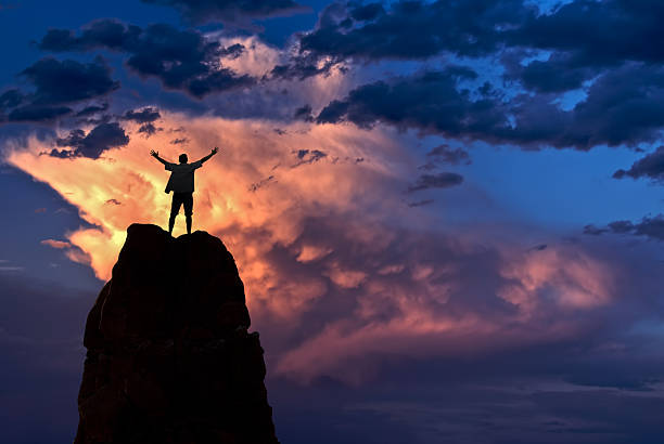 Man with arms raised in the sky winner success concept stock photo