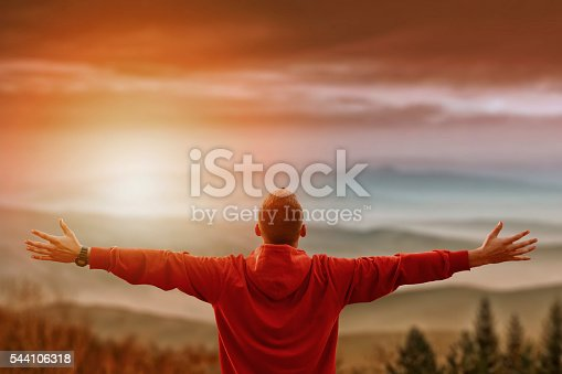 istock Man with arms spread looking at mountains 544106318