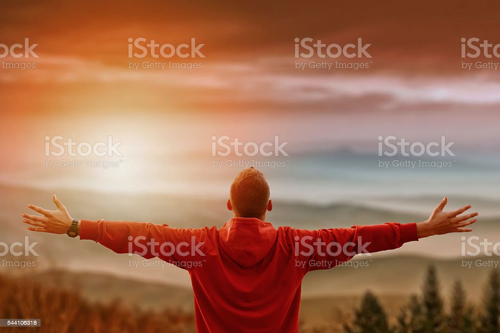 Man with arms spread looking at mountains stock photo