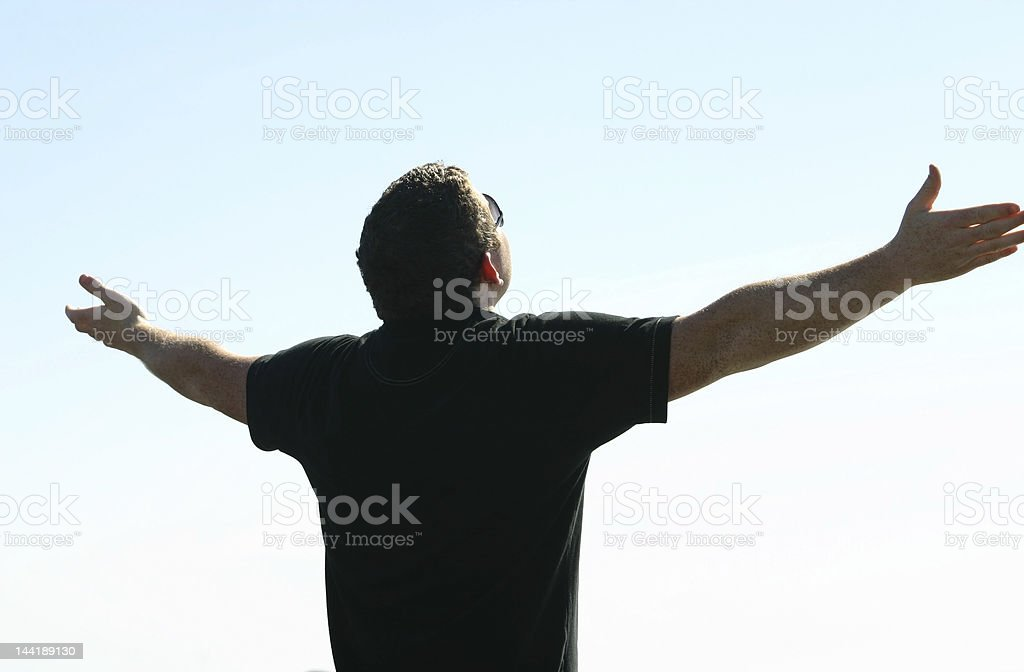 Man with arms wide in praise stock photo